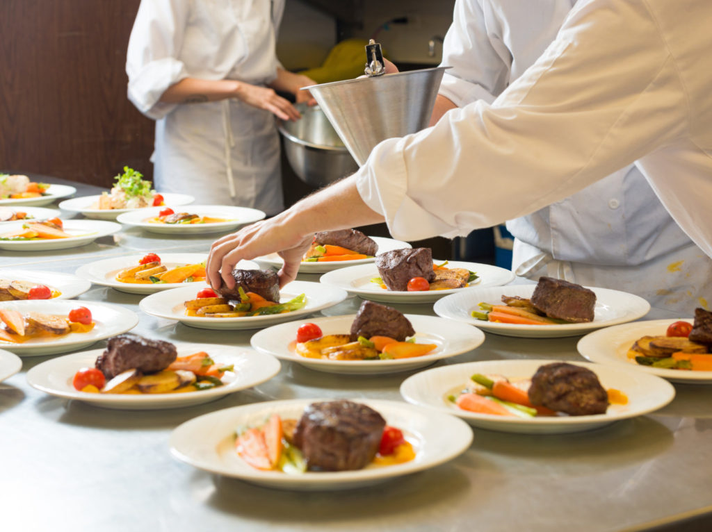 Chefs plating a grilled beef tenderloin dish