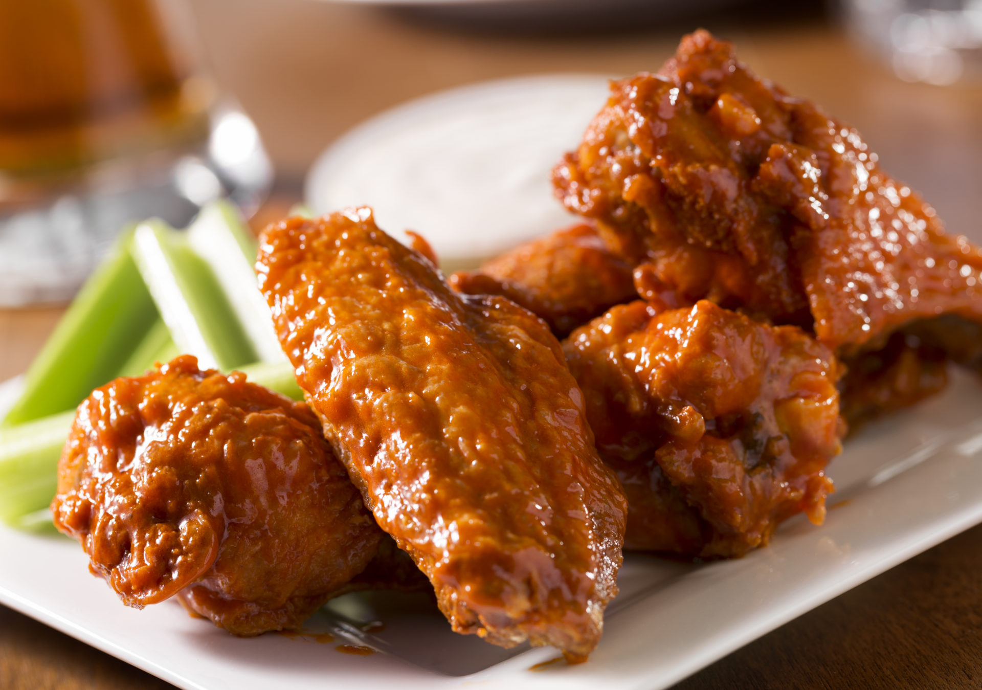 A plate of buffalo style chicken wings with celery and blue cheese with a beer on a table